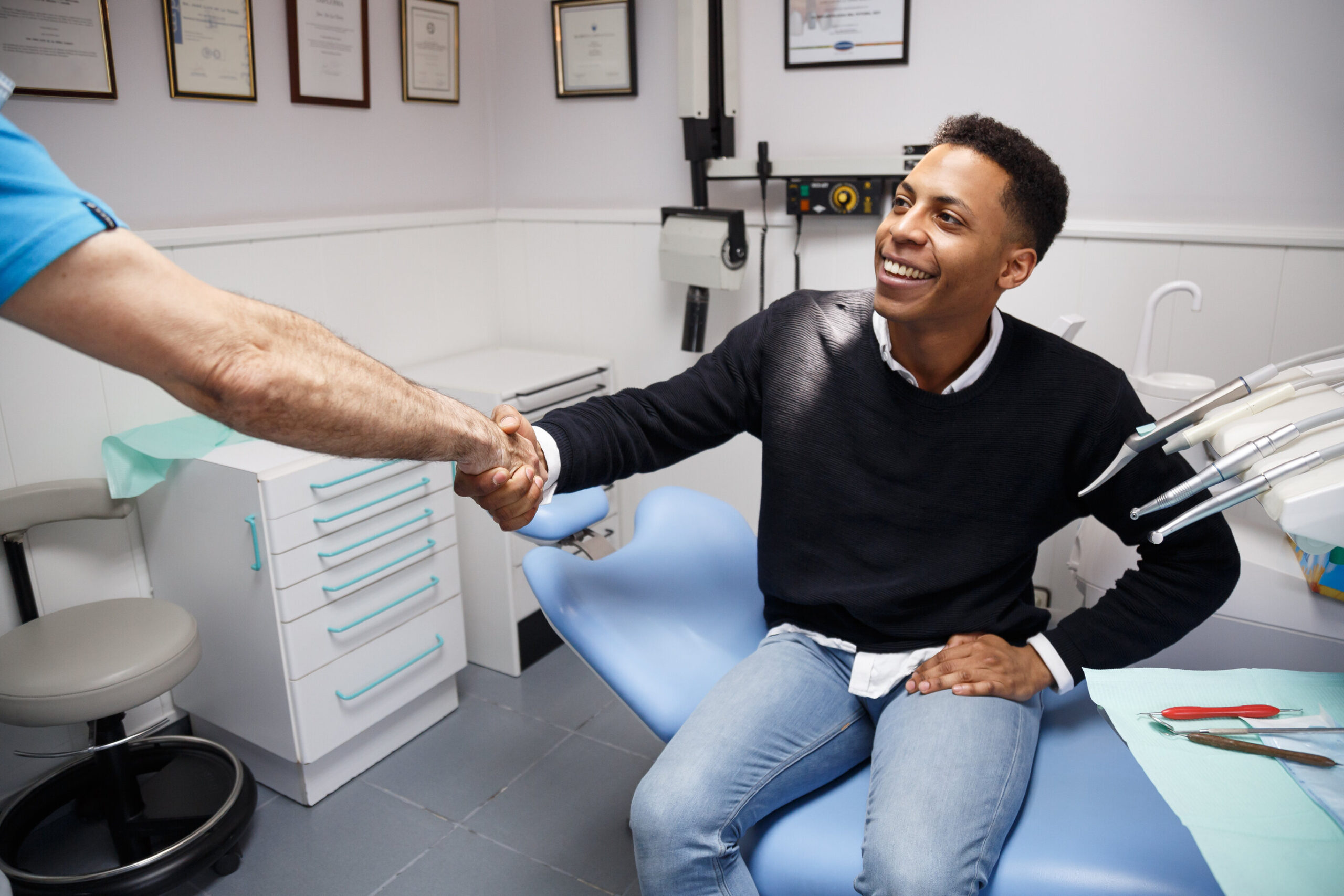 Young African-American man shaking hand of crop dentist having visit in medical clinic.